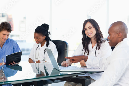 Two smiling medical interns working at the computer near colleag