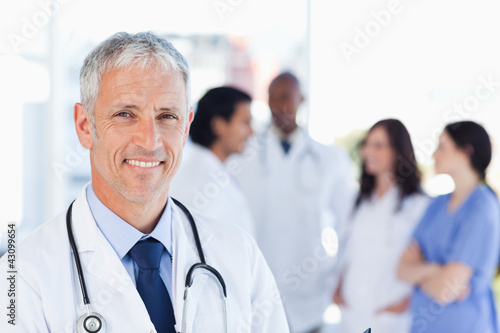 Mature doctor standing upright while waiting for his team Plakat