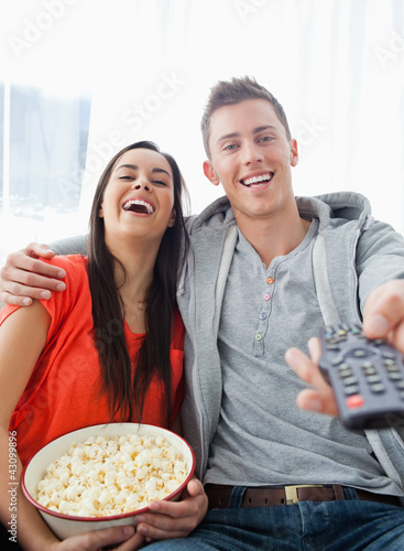 A laughing couple sitting on the couch with popcorn as they watc
