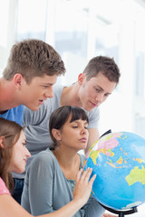Four students looking at the globe