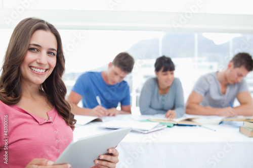 A smiling woman looking at the camera with a tablet in hand and