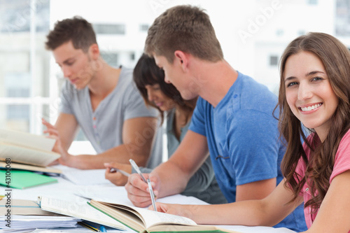 A side view of people studying as one girl looks into the camera