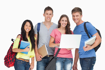 A smiling group of students holding a laptop while looking at th