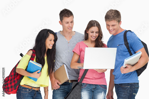 A group looking into a laptop and smiling