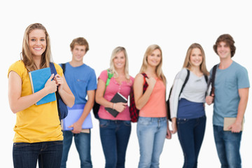 A group of college students standing as one girl stands in front