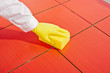 hand with yellow gloves and yellow  sponge clean red tiles