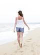 Woman in denim shorts walking on beach