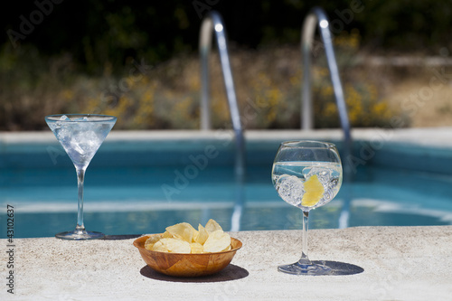 Aromatic gin tonic and mojito cocktails on swiming pool backgrou