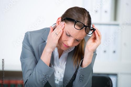 junge frau mit zahnschmerzen im büro