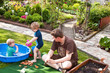 Young father playing with his children in summer garden