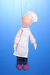 Wooden puppet as cook on blue background