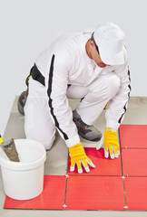 worker with bucket adhesive apply red tiles