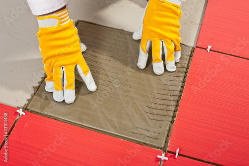 worker with a glass tile demonstrates how the tile adhesive work