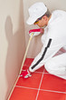 worker wrapped with masking tape red tiles