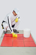 worker with yellow gloves and yellow  sponge clean red tiles