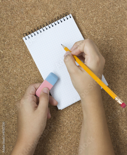 Pencil with eraser and notebook on cork. Two hands