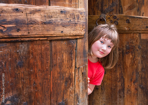Cute girl peeping behind an old wooden door