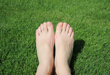 female feet on a green lawn
