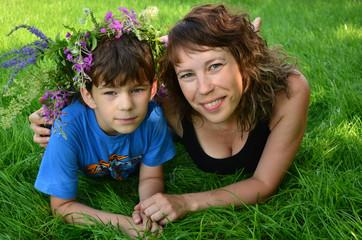 счастливые мама с ребёнком отдыхают на зелёной траве