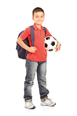 Full length portrait of a child with backpack holding a ball