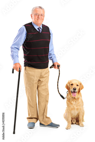 Full length portrait of a senior man holding a cane and a dog