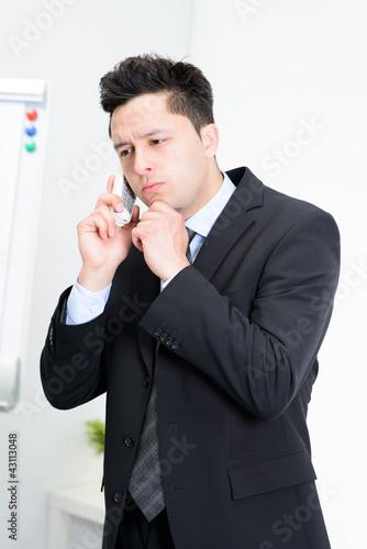 zweifelnder geschäftsmann am telefon