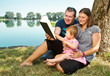 Happy family with books on the nature near lake