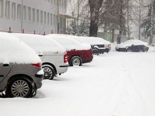 Snowy cars parked in a parking lots during blizzard