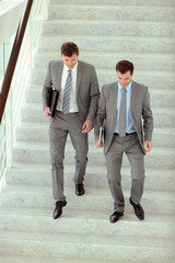Businessmen walking downstairs in office building