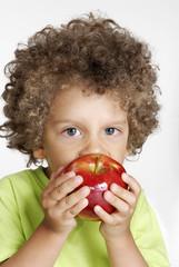 Niño comiendo una manzana roja,sujetando una manzana,fruta.