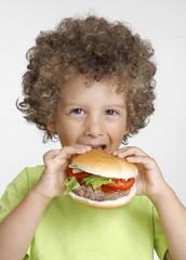 Niño comiendo hamburguesa,sujetando una hamburguesa.
