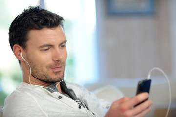Young man using mobile phone with handsfree headset