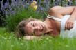 Junge Frau im Gras liegend