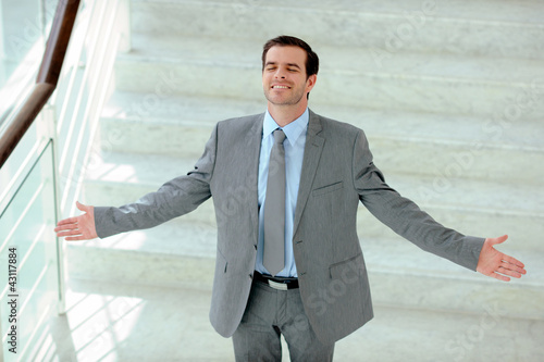 Satisfied businessman stretching arms out in stairs