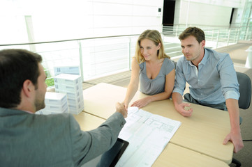 Couple in real-estate agency giving handshake to sales agent