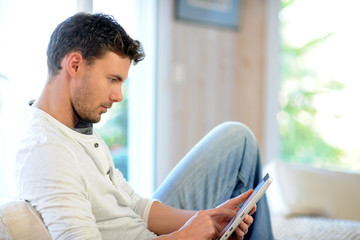 Handsome man relaxing at home with digital tablet
