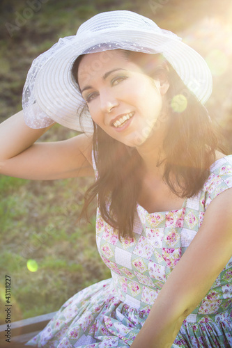 Happy woman in the park with hat under sunburst