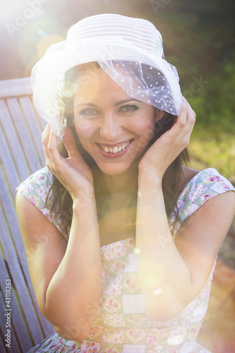 Happy woman in the summer season with hat in a park, with sunbur
