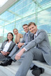 Cheerful business team sitting on stairs outside building