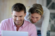 Couple laughing in front of laptop computer