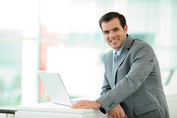 Businessman using laptop computer in entrance hall