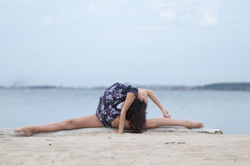 Young gymnast girl dance on beach