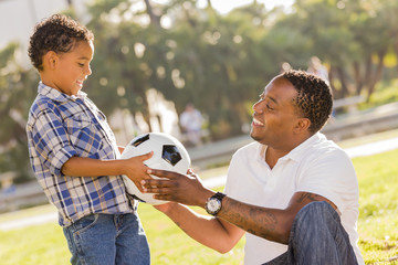 Father Hands New Soccer Ball to Mixed Race Son