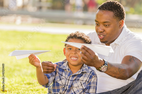 Mixed Race Father and Son Playing with Paper Airplanes