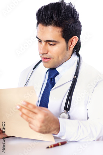 A male doctor sitting at the desk on white background