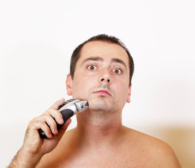 man shaving his beard off with an electric razor