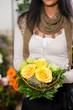 Floristin in Blumenladen mit Strauß Rosen