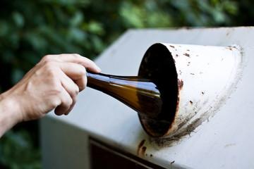 Entsorgung einer braunen Flasche in den Glascontainer