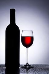 Rotwein Glas im Gegenlicht mit Weinflasche