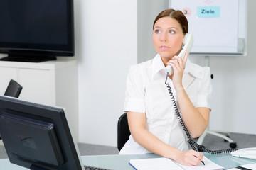 sekretärin sitzt an ihrem arbeitsplatz und telefoniert